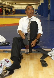 U.S. President Obama puts his shoes back on after meeting wrestlers on the mat as he visits the U.S. Olympic Training Facility in Colorado Springs